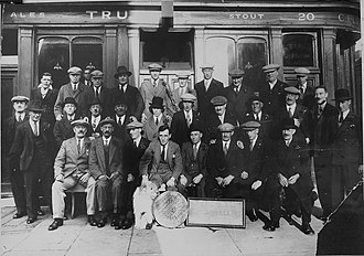 "Darts - ""Hope and Anchor dart club"", Hope and Anchor, 20 Waterloo Street (now Macbeth Street), Hammersmith, London, UK. c.1925. NB publican Charles Fletcher (seated front row centre) with elm board"