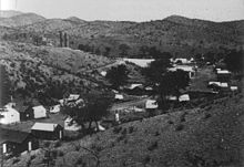 A street of about 30 one-story buildings stretches along the floor of a dry, narrow valley. A few trees grow near the houses, but only low, widely separated desert shrubs grow on the hills above the valley. Two smokestacks belonging to the Hermosa Mill are visible just over the nearest hill.