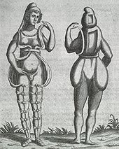 A front and back illustration of a Renaissance-era hermaphrodite showing a person with female facial features, breasts, and what appears to be a small penis or large clitoris. She wears a small hood and open robe tied multiple times around the legs. Where it opens in the front, the apparent rear appearance shows it to be perhaps a shell of some kind, as one with her body Two squares are missing from her the back of her head and torso, she has no buttocks.