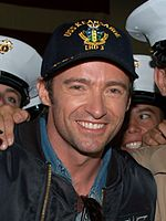 A man smiles for the camera as he wears a dark-colored jacket over a jean shirt and a cap possessing a navy emblem. He is surrounded by figures wearing white peaked caps, who are mostly cropped out of view.