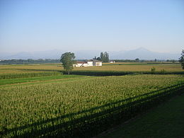 Photo of a rural scene with a farmhouse and crops in the foreground and mountains in the distance.