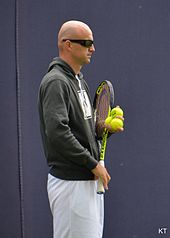 Ivan Ljubičić standing in athletic gear and sunglasses, holding a racquet in his right hand and three balls in his left hand.