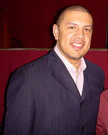 A man with short hair wearing a blue suit jacket and white shirt