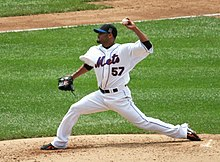 "A man in a white baseball uniform with the word ""Mets"" written across the chest delivers a pitch."