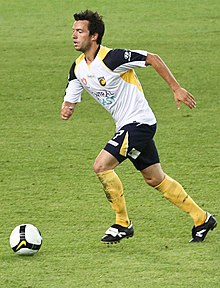 A man with dark hair in a white shirt and navy shorts running towards a football
