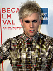 A shot of Justin Tranter, peering into a nearby camera.