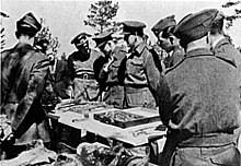 British, Canadian, and American officers (POWs) brought by the Germans to view the exhumations Katyn massacre 4.jpg