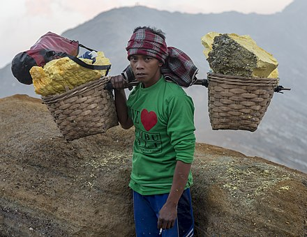 Sulfur miner with 90 kg of sulfur carried from the floor of the Ijen Volcano (2015) Kawah-Ijen Indonesia Ijen-Sulfur-Miner-01.jpg