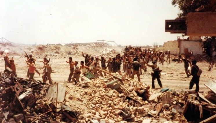 Prisoners of war walking through desert-war devastation