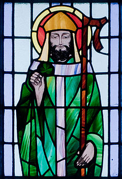 A stained glass window depicts Saint Patrick dressed in a green robe with a halo about his head, holding a sham rock in his right hand and a staff in his left.