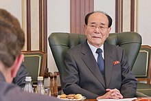 Kim Yong Nam seated in a suit, wearing a ceremonial pin for North Korea