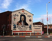 "Mural on a gable wall showing William of Orange and the date of the Battle of the Boyne, with the legend ""Welcome to Sandy Row""."