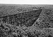A black and white aerial photo of a bridge crossing a valley
