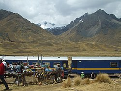 "The train ""The Andean"" at La Raya Station with market stalls and the mountain Chimpulla in the background, Layo District-Santa Rosa District"