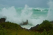 Sea spray fills the air amid high waves breaking on rocky coastline