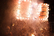 Two men dressed as colonial soldiers carry a banner, exploding with firecrackers, commemorating Guy Fawkes and his co-conspirators as part of Lewes Bonfire Night celebrations.