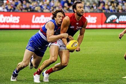 Western Bulldogs player Liam Picken tackling Jordan Lewis of Melbourne, who is attempting a handball Liam Picken tackling Jordan Lewis while handballing.jpg