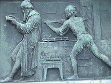Relief Druckerwerkstatt am Gutenberg-Denkmal (Mainz) (Quelle: Wikimedia)