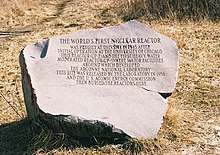 "Image of the granite marker. The text reads: ""The world's first nuclear reactor was rebuilt at this site in 1943 after initial operation at the University of Chicago. This reactor (CP-2) and the first heavy water moderated reactor (CP-3) where major facilities around which developed the Argonne National Laboratory. This site was released by the laboratory in 1956 and the U.S. Atomic Energy Commission then buried the reactors here."""