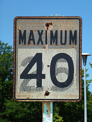 "Metrication in Canada - A long-ago metricated speed-limit sign in Bolton, Ontario, with the old ""25 mph"" value now showing through the 40 km/h limit"
