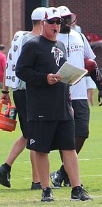 Candid photograph of Smith standing on a football field with a whistle in his mouth holding a pen and a laminated sheet of paper in his right hand and wearing black shorts, a black long-sleeved t-shirt and a white baseball cap all of which bear the logo of the Atlanta Falcons
