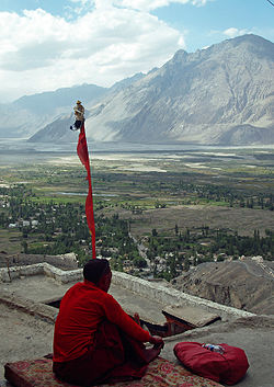 A monk meditates on terrace of Diskit Monastery, with Nubra Valley and Diskit village seen in the background