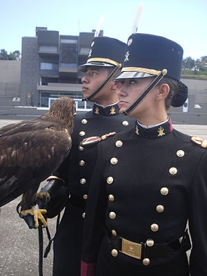 Heroic Military Academy (Mexico) - Another cadet holding the golden eagle mascot. A female cadet stands in the foreground. Both wear the gala uniform of the Cadet Corps