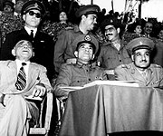 Three men seated and observing an event. The first man from the left is wearing a suit and fez, the second man is wearing a military uniform, and the third man is wearing military uniform with a cap. Behind them are three men standing, all dressed in military uniform. In the background is ab audience seated in bleachers