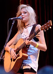 Nina Nesbitt toting an acoustic guitar before a microphone on a stand.