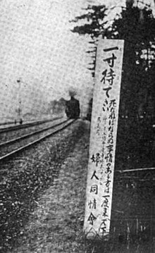 A black-and-white image of a tall signboard with Japanese writing (larger at the top), next to train tracks. There is a train visible in the distance.