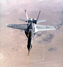 Jet fighter over-flying desert. The jet has black nose and two outward-canted vertical stabilizers between which lay two engines.