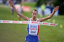 A young man representing France lifts his arms as he breaks the tape at the finishing line of a race.