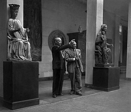 Stanisław Lorentz guides Pablo Picasso through the National Museum in Warsaw in Poland during exhibition Contemporary French Painters and Pablo Picasso's Ceramics, 1948. Picasso gave Warsaw's museum over a dozen of his ceramics, drawings and colour prints. Pablo Picasso in NMW.jpg