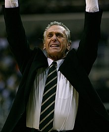 Pat Riley, en costume, les bras en l'air.