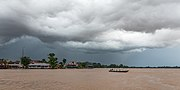 Pirogue on the Mekong under grey clouds before a storm.jpg