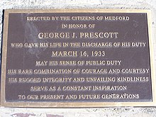 Black plaque with gold letters commemorating George J. Prescott