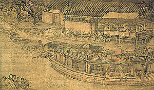 A close up view of a large trading barge crewed by multiple people. The barge has wooden walls surrounding it on all sides, and a thin line of tiled roof capping the walls, but not covering the interior of the ship. There are several windows built into the wall of the vessel.