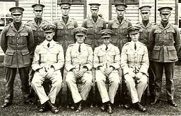 Portrait of eleven men in military uniforms with peaked caps, seven standing and four seated