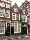foto van Langgerekt smal huis met aan de voor- en achterzijde puntgevel met vlechtingen. Voorgevel beklampt. Goede pui. Gotische houtskelet