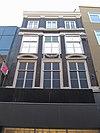 foto van Pand met pilastergevel waarvan de top in recente lijst is afgeknot tot attiekverdieping. Vensterfrontons en festoen