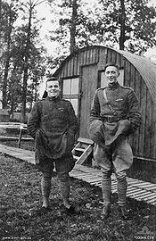 Two men in military uniform standing side-by-side. The man on the left if short and stocky, while the man on the right is tall and thin. In the background is a cabin.