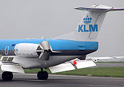 A Fokker 70 of KLM landing with flaps fully extended, spoilers raised, and reverse thrust selected.  The two reverse thrust buckets behind each engine can be seen in the deployed position, diverting the engine exhaust gases forward