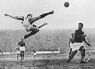 Photograph of a man who is about to strike a football in mid-air