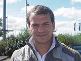 A head-and-shoulders photograph of a man with short brown hair wearing a grey jacket over a white shirt.