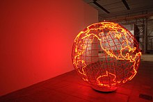 To the right of a red wall, a steel sphere glows along the edges of the Earth's continents.