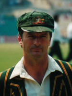 Middle-aged man around 30 wearing a baggy green cap with the Australian coat of arms, Australian blazer, green with yellow stripes, and a cream cricket shirt. He is clean shaven and has brown hair.