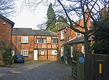 A cobbled courtyard with brick buildings on three sides, some of them timber-framed. On the gatepost on the right is a blue commemorative plaque