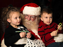 Santa Claus talks to two children to the left and right of him.