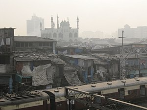 Dharavi - Shanty dwellings next to railway tracks in Dharavi (about 2010). A mosque inside the slum is visible. The railway network provides mass transit to the slum residents.