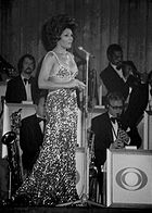 Shirley Bassey performing in front of a brass section.